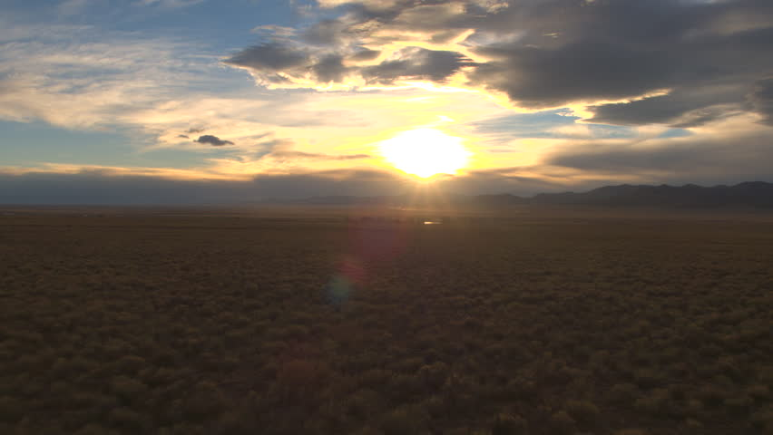 AERIAL: Flying above vast grassy field into the dramatic golden light sunset with majestic Rocky Mountains in the distance. Wild nature in spectacular remote desert valley, Great Plains, United States   Shutterstock HD Video #26178206