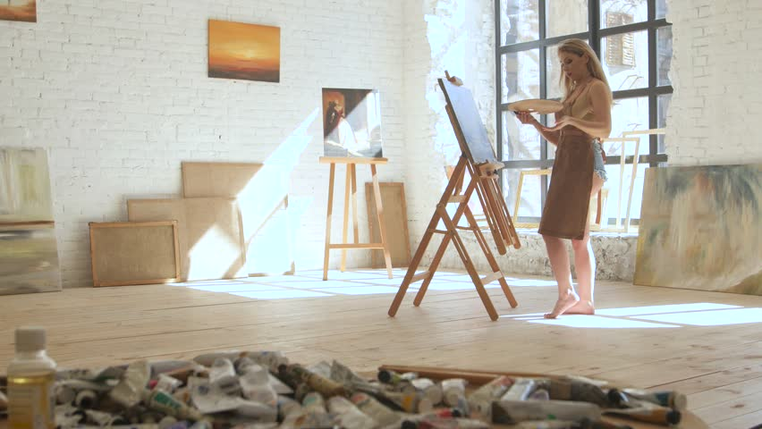 Woman artist paints on canvas on easel and holds palette in art workshop | Shutterstock HD Video #26184830