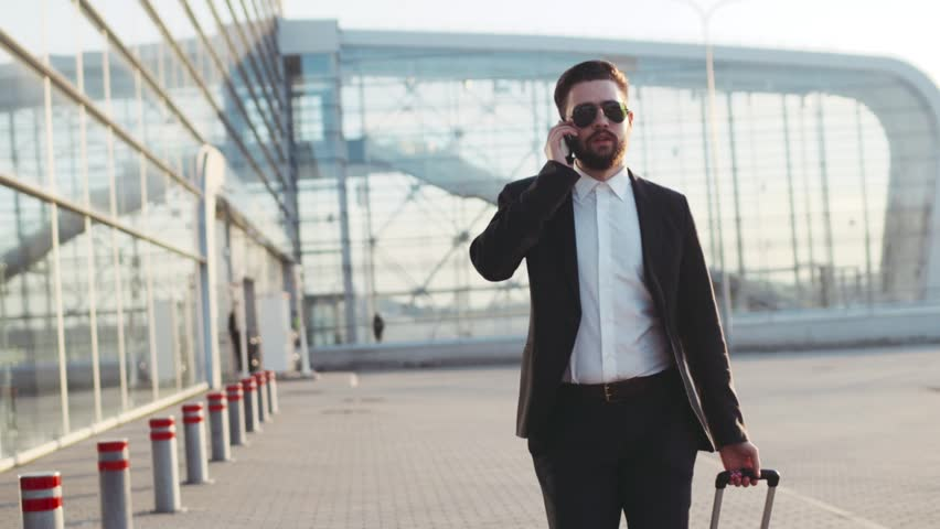 Young stylish man in sunglasses talking on his phone, and pulling suitcase while exiting the airport. Successful life. Business style, traveler, modern lifestyle. Active lifestyle. | Shutterstock HD Video #26209031