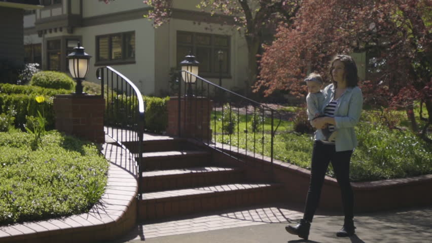 Happy Mom Goes For A Walk With Her Baby In Nice Neighborhood On Sunny Spring Day | Shutterstock HD Video #26217941