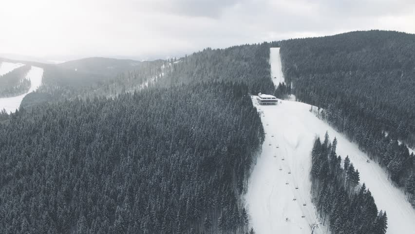 4K Aerial Drone View: Flight over winter mountains in the snowfall. Ski slopes with pine tree forest around. Majestic nature landscape. Holidays in Ski Resort Bukovel, Carpathian Mountains, Ukraine | Shutterstock HD Video #26218751