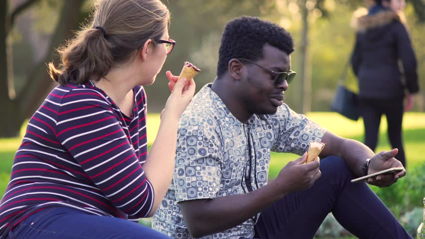 Interracial young attractive happy couple, natural picnic date in Spring / Summer eating ice cream and talking, mobile phone scrolling. Sunny day, beautiful nature, relaxing. White Caucasian and Black | Shutterstock HD Video #26219021