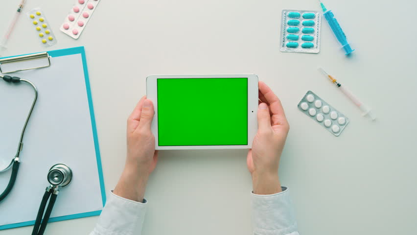 Doctor seaching something on tablet with green screen. Chroma key. Top view. White background | Shutterstock HD Video #26226203