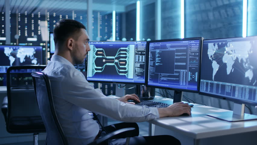 System Security Specialist Working at System Control Center. Room is Full of Screens Displaying Various Information. He Shares His Opinions with Colleagues. Shot on RED EPIC-W 8K Helium Cinema Camera.