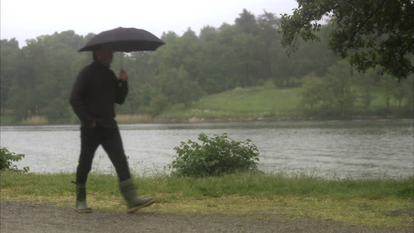 A man with an umbrella walking by water - HD stock video clip