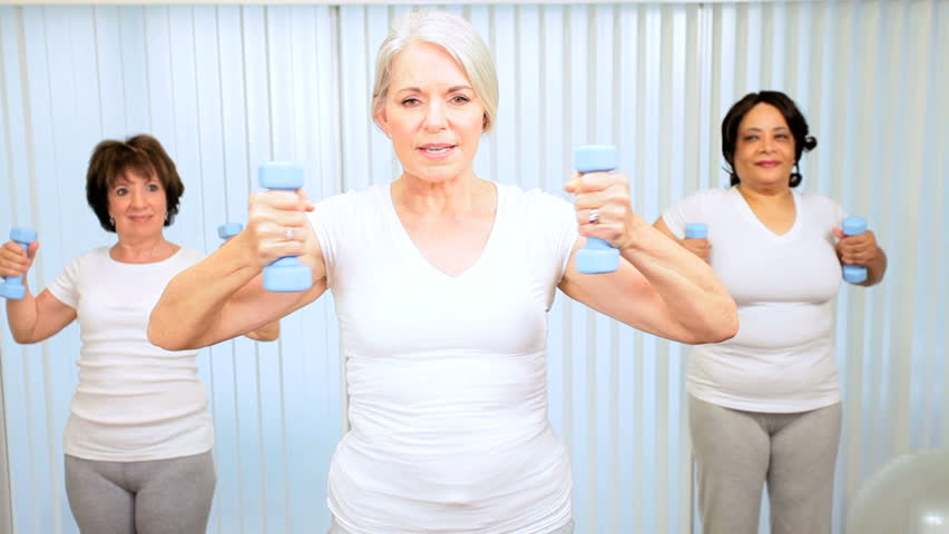 Mature group retired females using weights exercise health club - HD stock footage clip