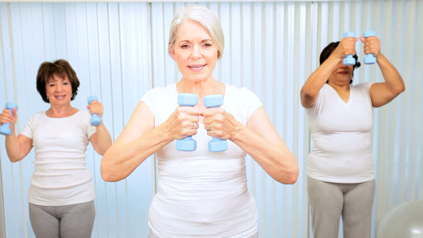 Elderly female gym members using weights yoga fitness class - HD stock footage clip