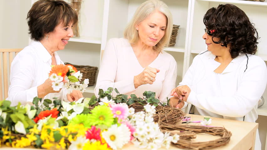 Multi ethnic older female friends crafting silk flowers - HD stock footage clip