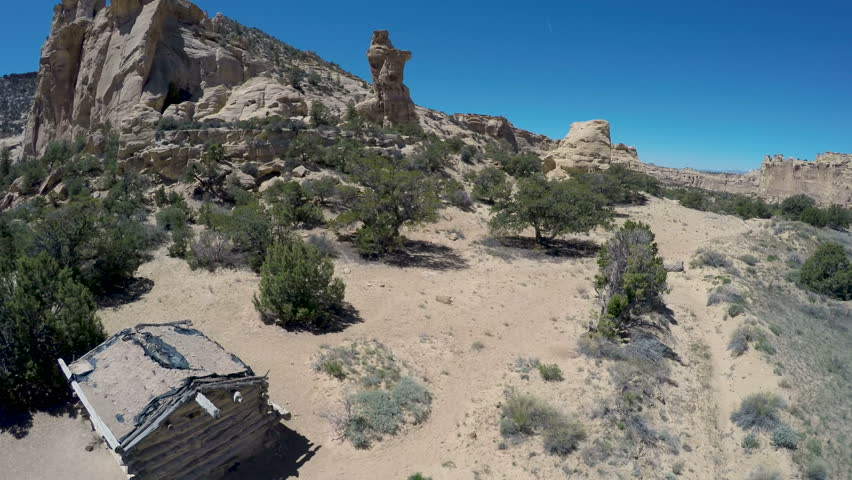 Aerial-Flying over historic pioneer cabin to distinctive sandstone monolith and the rugged geology of the San Rafael Swell in the desert of southeast Utah