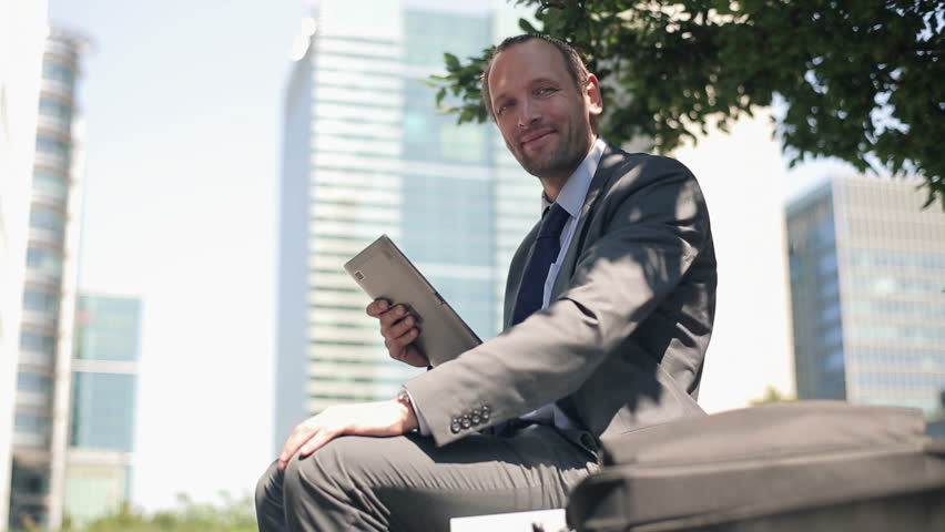 Happy businessman with tablet computer in the city