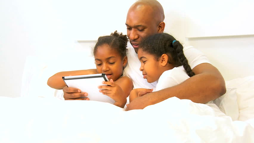 African American father relaxing bed young daughters wireless tablet
