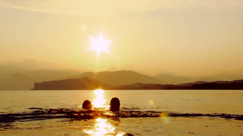 Two women swimming in the sea at sunset. - HD stock video clip
