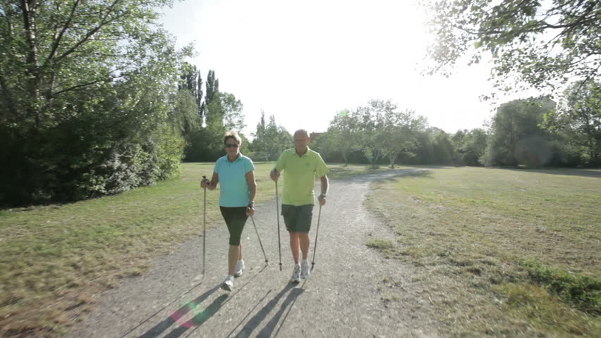 following happy senior nordic walking couple on path in park