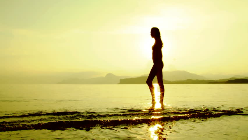 Silhouette of a beautiful women standing on the beach in sun rays.