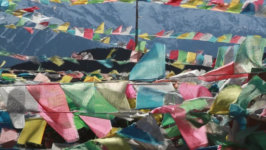 Buddhist prayer flags fly in the wind near the mountain - HD stock footage clip