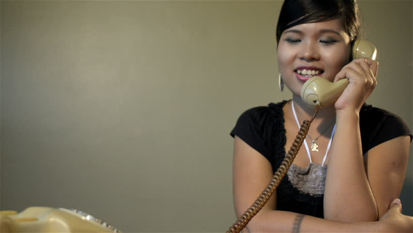 Vintage style clip of young Asian woman answering the phone - tracking shot. - HD stock video clip