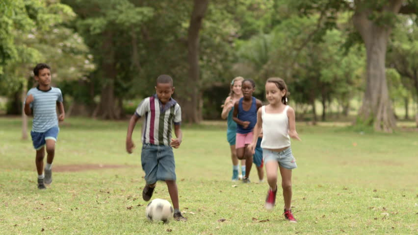 Multiethnic boys and girls playing european football, american soccer in city park. Summer camp fun - HD stock footage clip