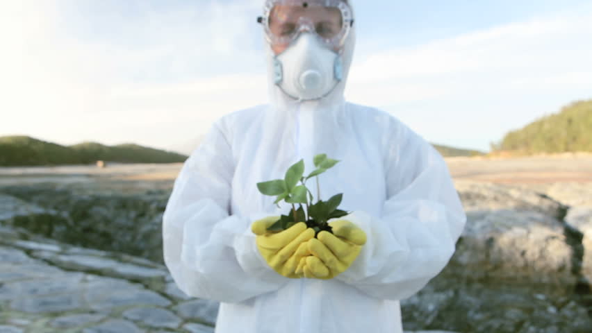 Chemical engineer showing a small new plant in the hands