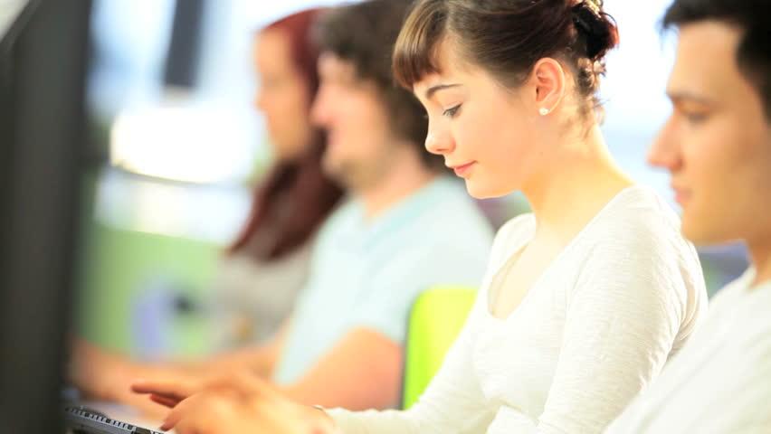 Caucasian female classmate using online computer degree exam in college classroom