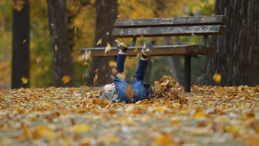 Running seven year old boy throws autumn leaves and falls to the ground. slow motion.