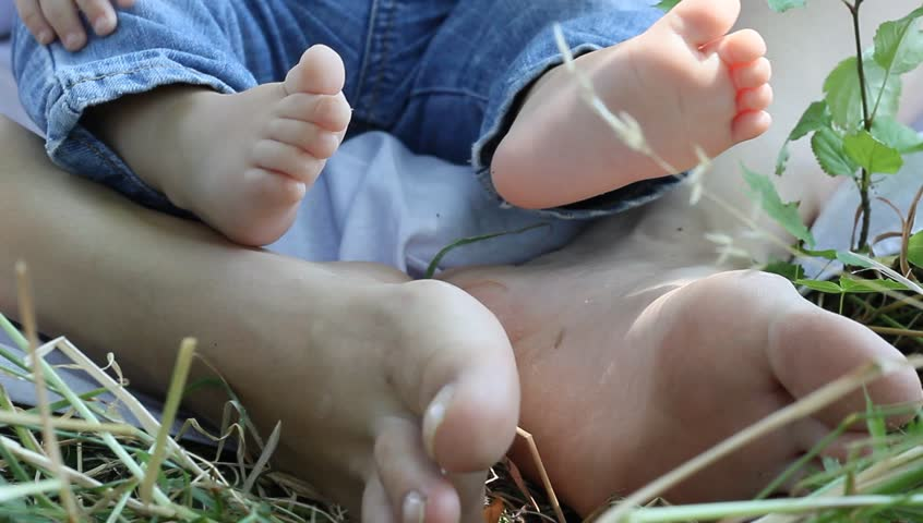 Parent and child feet enjoying the spring in the garden - HD stock footage clip
