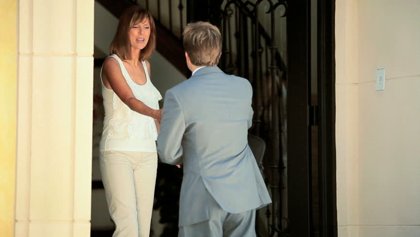Caucasian family opening door luxury home to successful male realtor