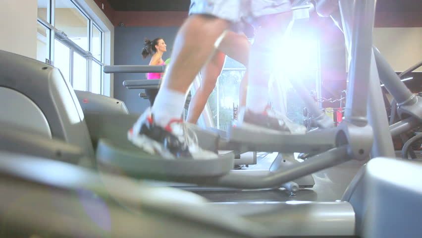 Legs only foreground people exercising on modern equipment in health club - HD stock footage clip