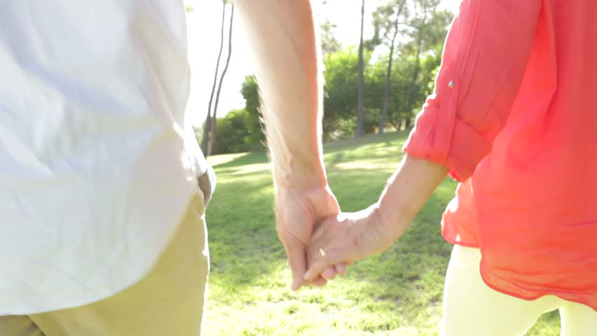Romantic senior couple holding hands as they walk along country path.