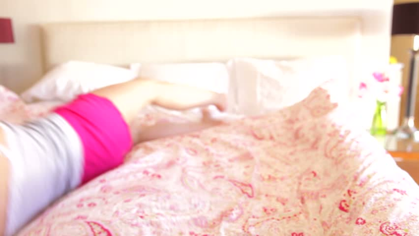 Woman rolls into frame on bed before looking into camera and smiling. - HD stock footage clip