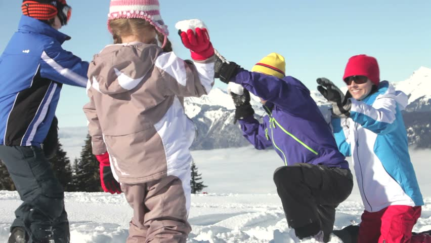 Mother, father and two children throwing snowballs and laughing. - HD stock video clip