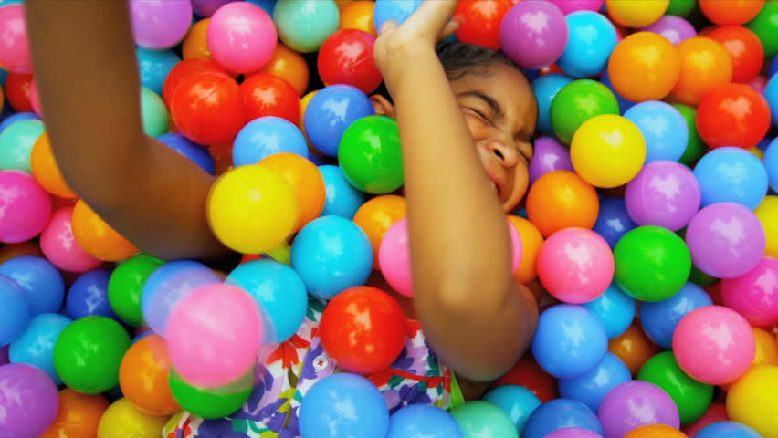 Laughing young ethnic girl playing in plastic pool full colourful balls shot on RED EPIC