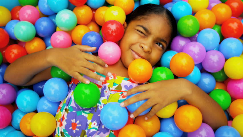 Cute young African American girl covered in multi coloured plastic balls in big paddling pool shot on RED EPIC