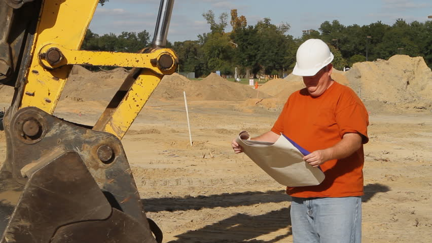 Construction foreman stands by heavy machinery at an excavation site and sends a text message after reading some blueprints. - HD stock video clip