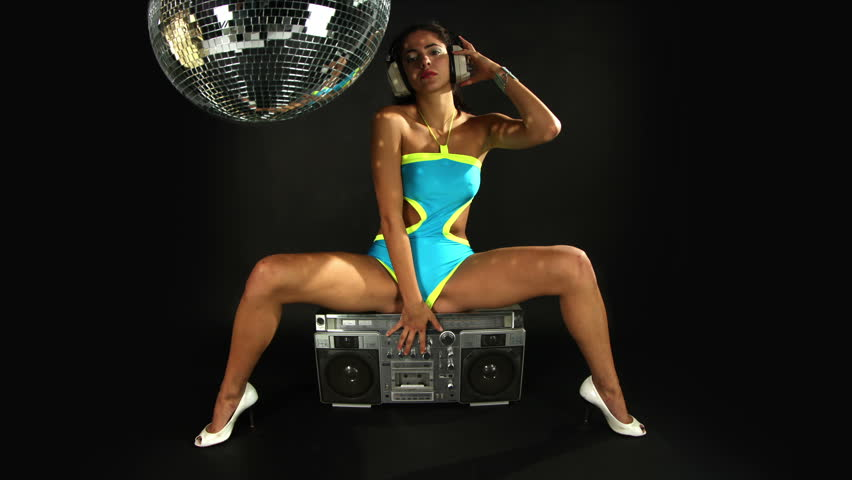 sexy young woman dances and poses sitting on a hifi speaker with 2 retro gramophones under her feet