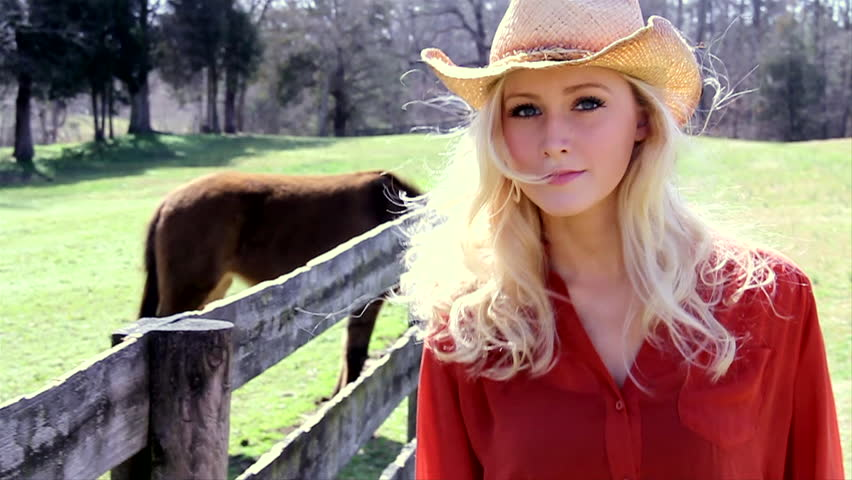Cowgirl walks down a fence line. slow motion.