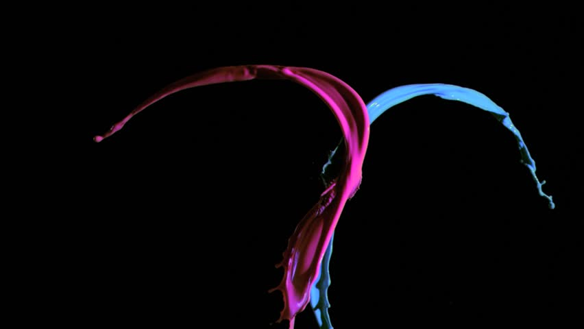Blue and pink paint in super slow motion being thrown against a black background