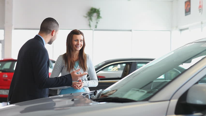 Businessman showing a car to a woman in a dealership