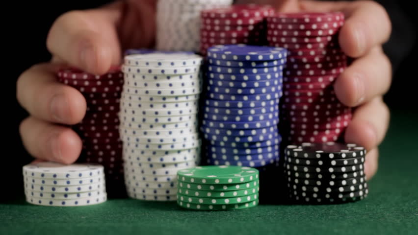 Pushing poker chips toward camera