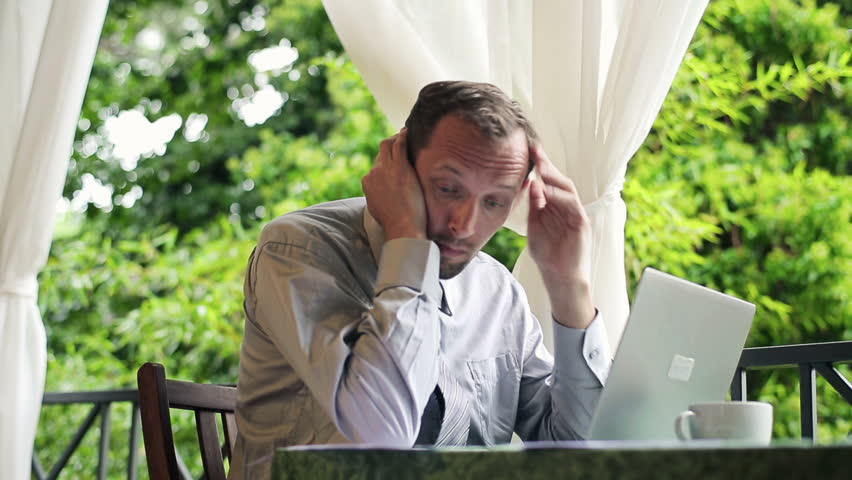Businessman with laptop and documents reading bad news on terrace
