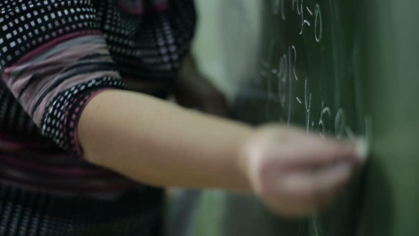 Teacher wrote in chalk on a blackboard