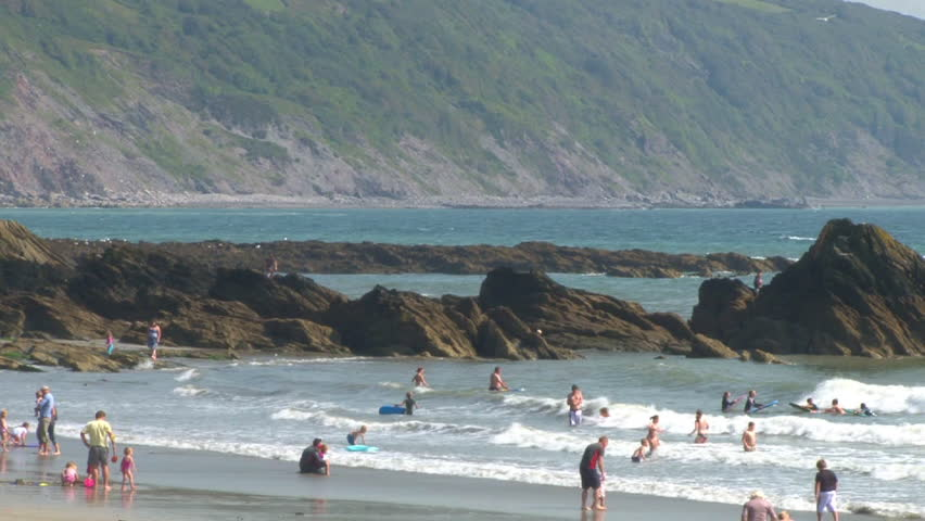 Vacationers and holiday makers playing in the water on a beach in Looe, Cornwall.