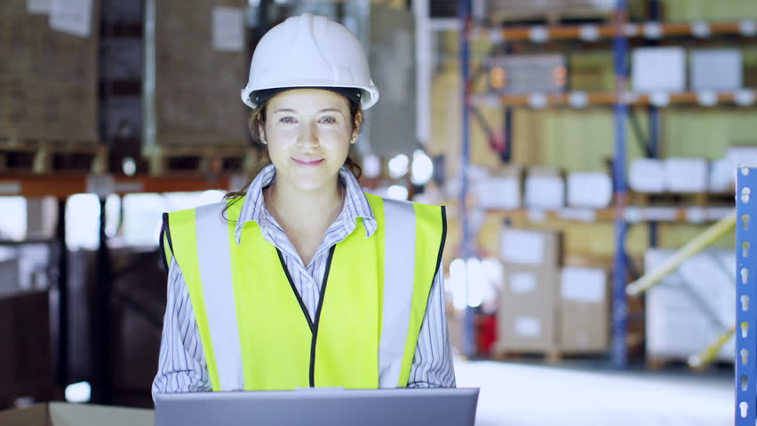 An attractive female warehouse employee wearing high visibility clothing and a hard hat looks up from her laptop to smile at the camera. Other warehouse employees can be seen working in the background