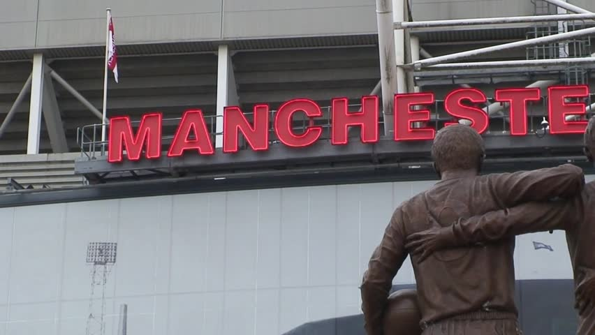 MANCHESTER, UNITED KINGDOM - CIRCA 2011: Pan of the Neon Manchester United sign at Old Trafford with the Charlton, Law and Best Statue in the foreground.