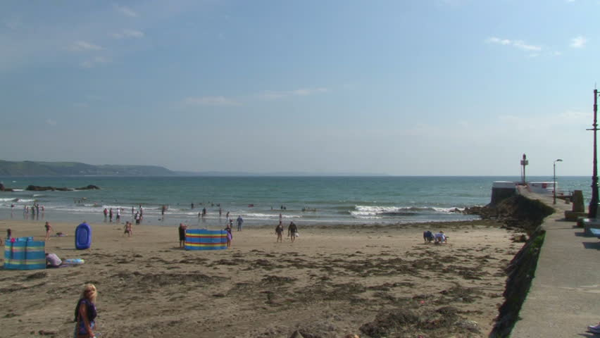 LOOE, ENGLAND - CIRCA 2011: Holiday Makers enjoying a sunny day on West Looe beach in Cornwall.