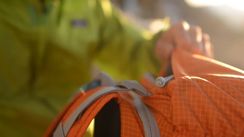 Close up as a hiker packs and prepares his orange backpack for a winter hike in the snow during the day
