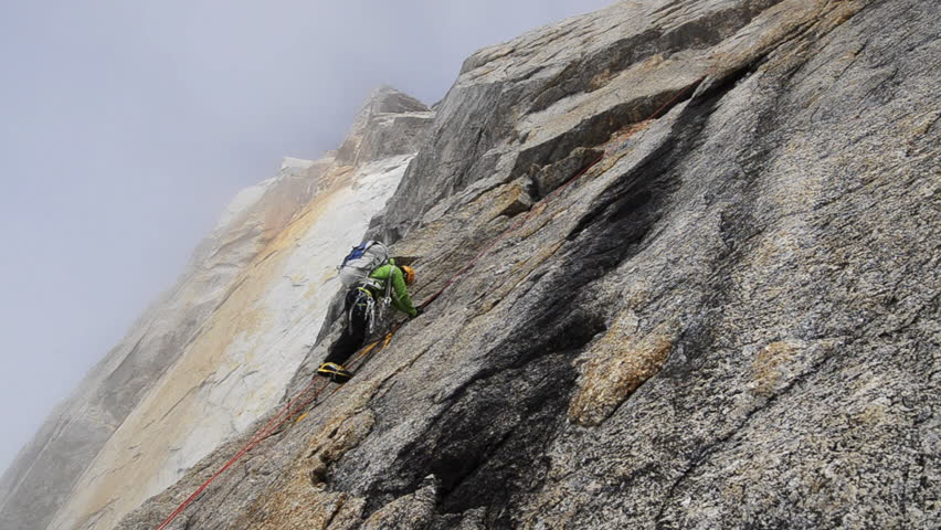 A climber with a backpack ascending a sheer rock face on his way to a mountain peak in the Alaskan wilderness during the day