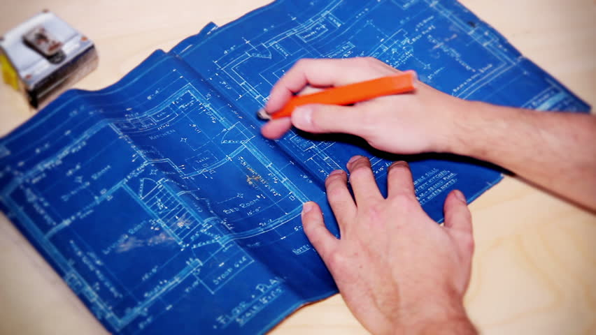 A carpenter examines a house's blueprints.