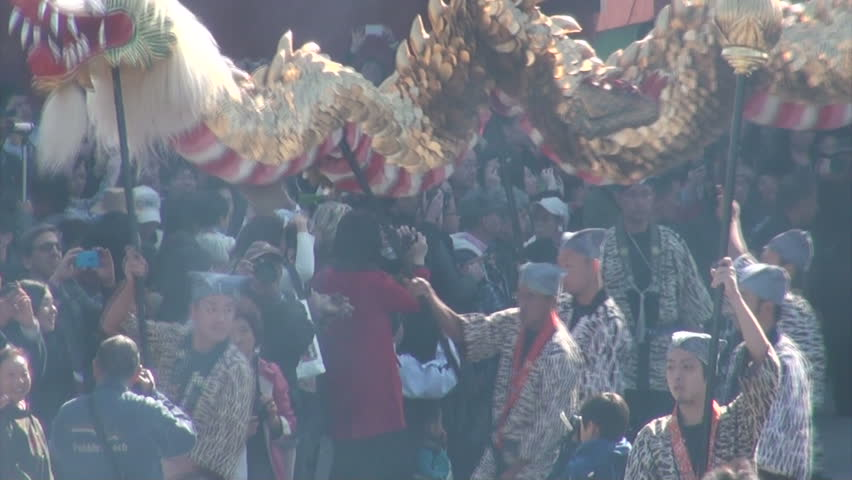 TOKYO, JAPAN - 3 NOVEMBER 2012: Japanese devotees are carrying a large dragon through the streets while smoke coming from an incense burner blurs their vision at the Sensoji temple complex in Tokyo - HD stock footage clip