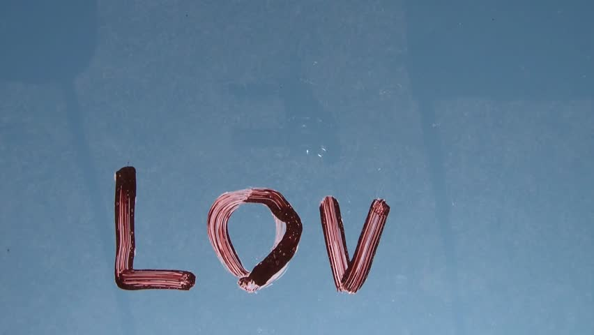 The word love is painted on glass while being shot from underneath towards the blue sky. - HD stock footage clip