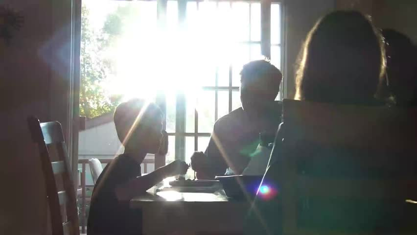 Silhouetted family eating dinner while lit from behind by sunshine piercing through glass patio door, includes mother, father, son, and daughter.